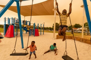 Residents from Ellenbrook play on swings at the Brown Park recreation complex evacuation centre in Perth.