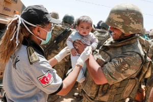 A Turkish soldier and a health officer helping a Syrian baby on the Syrian side of the border