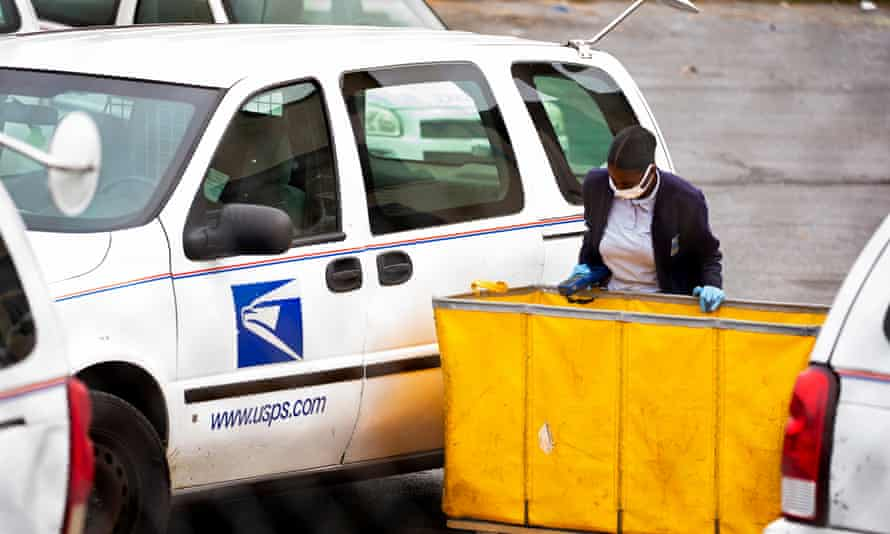 A USPS employee wearing a protective face mask loads mail into a vehicle to be delivered at a post office in Washington DC on 28 April 2020.