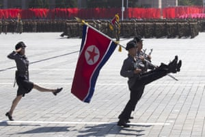 Soldiers march with the North Korean flag