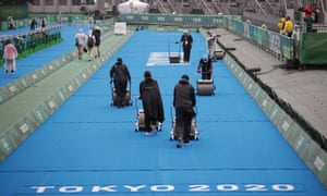 Workers during rainy weather prepare the track for the women's triathlon at the Tokyo Olympics.