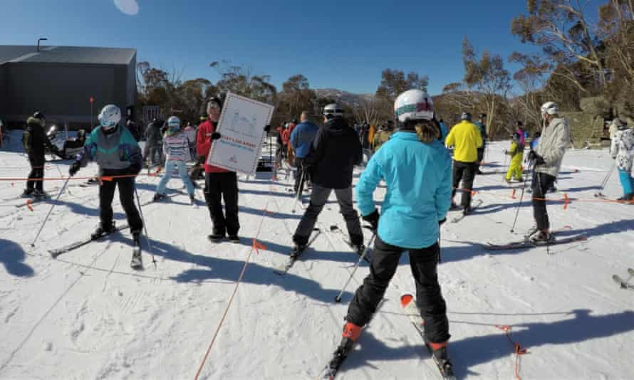 Social distancing on the slopes, an employee surrounded by skiiers at Merritts in Thredbo holds up a sign instructing people to remain 1.5m apart.
