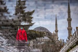 A tourist is reflected on a puddle near the Blue mosque on the first day of Ramadan in Istanbul