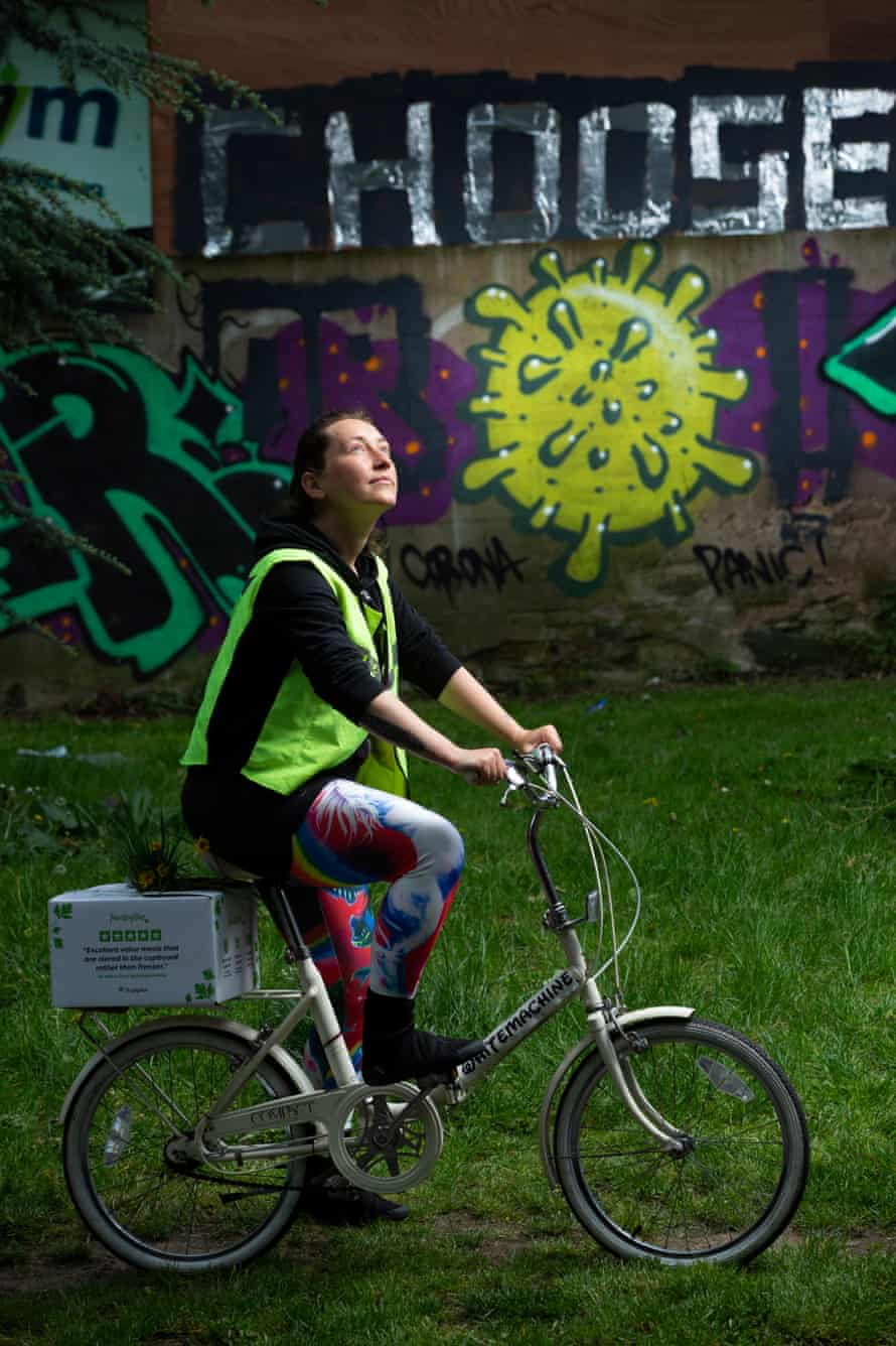 Anna Janiszewska, who works for a food distribution company, with her new bike by a coronavirus mural