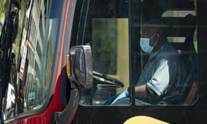A bus driver wears a face mask as he drives a Washington Metropolitan Area Transit Authority bus on 15 April 2020 in Washington DC.