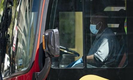 A bus driver wears a face mask as he drives a Washington Metropolitan Area Transit Authority bus on 15 April 2020 in Washington DC.