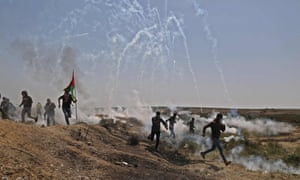Palestinians run for cover from tears gas canisters fired at them east of Gaza City in the Gaza strip.