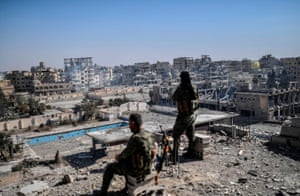 Raqa, 2017 Fighters from the Syrian Democratic Forces stand guard on a rooftop