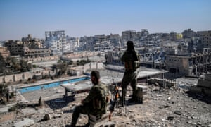 Fighters of the SDF stand guard on a rooftop and look out over the shattered city