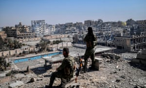 Syrian Democratic Forces fighters stand guard in Raqqa on 20 October after retaking the city from Isis militants.