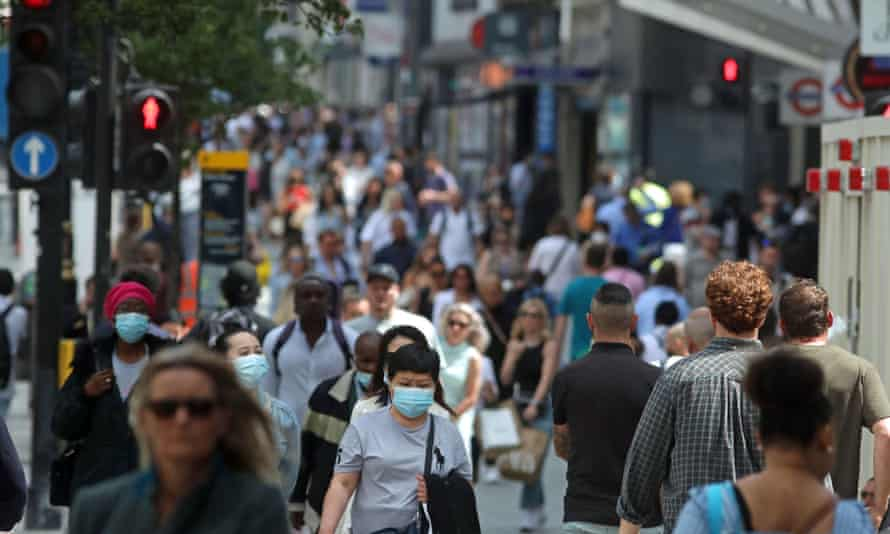 Some people wearing masks as they walk down busy Oxford Street, London.