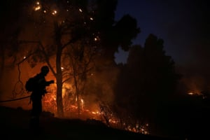 Kechries, Greece: A firefighter sprays water on a wildfire burning near the village.