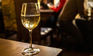 Half full white wine glass on a table in a pub