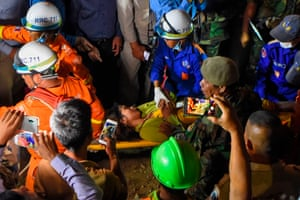 Rescuers carry a survivor out of the rubble on Saturday