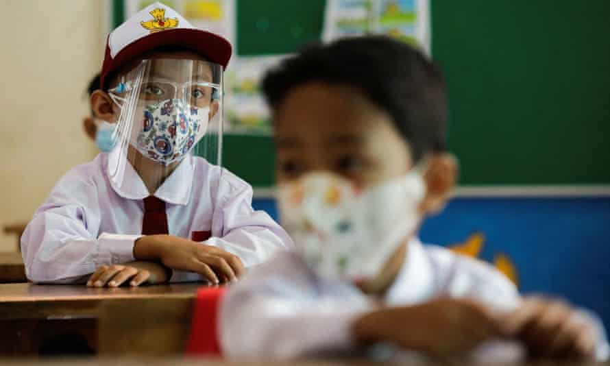 Elementary school students wearing face masks and face shields attend class in Jakarta