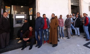 Libyans wait to withdraw money from an ATM machine outside a bank in the capital Tripoli.