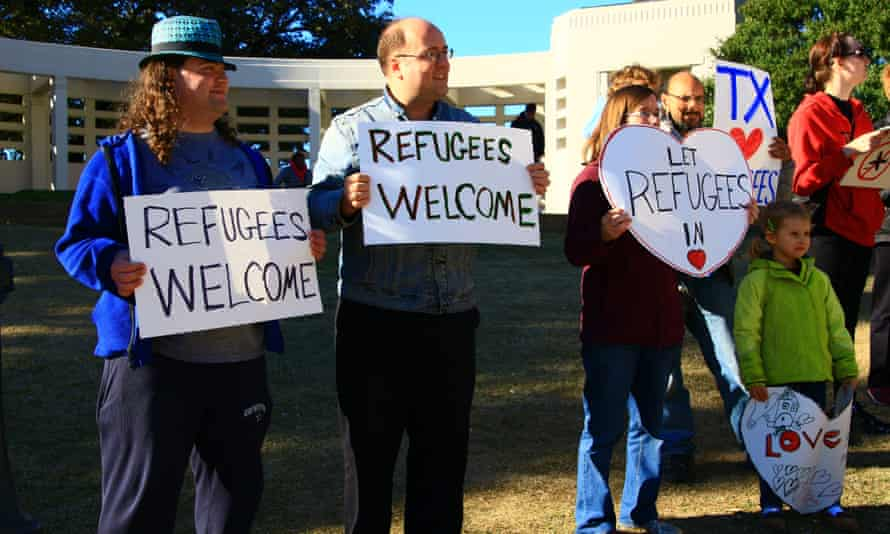 Human rights activists hold placards welcoming refugees to Dallas, and all of Texas, on 21 November.