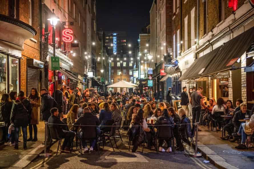 Customers eat and drink on the street outside a bar ahead of a coronavirus shutdown in Soho