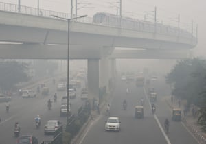A train and vehicles in smog in New Delhi, India