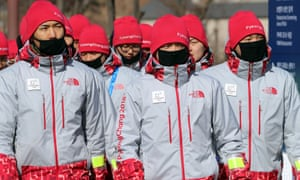 Volunteers protect their faces from the cold at the Olympic stadium in Pyeongchan