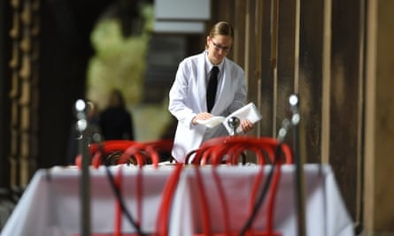 A waitress sets a table at a restaurant in Sydney.