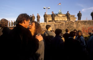 A couple laugh together on the west side of the Berlin Wall as people began crossing into the other half of the city in 1989