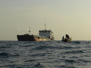 A local fishing boat off the coast of Tanzania is dwarfed by a large industrial trawler