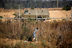 A Palestinian man on crutches watches as an Israeli military vehicle drives near the fence along the border with Israel.