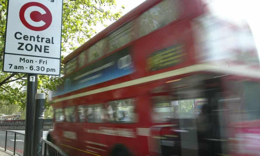 A double-decker bus passes a congestion zone sign in central London.