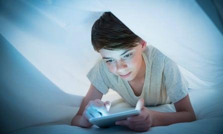 Boy using digital tablet under sheet