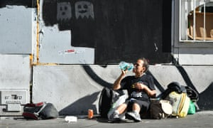 A homeless woman drinks mouth wash along a sidewalk in downtown San Francisco, California