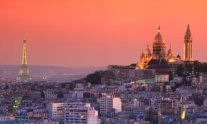 The Sacré-Cœur and Eiffel Tower in Paris at dusk.
