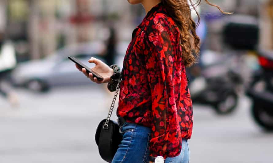 A woman walks down a street in Paris on her mobile phone.