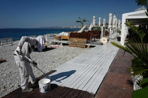 Nice, France: a worker paints wooden boards at Beau Rivage private beach in the French Riviera city