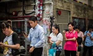 Hong Kong commuters look at their mobile phones as they wait in line for a bus.