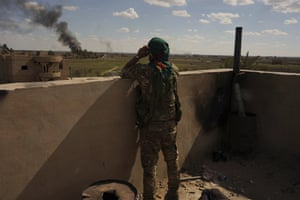 A fighter with the US-backed Syrian Democratic Forces (SDF) watches black smoke billow from the last small piece of territory held by Islamic State militants as the area is pounded with artillery fire and occasional airstrikes