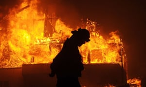 A fireman walks past a burning house in Ventura, California. Wildfires in the state have been made more violent by a cycle of drought and heavy rainfall.