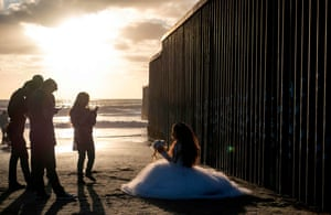 A girl celebrating turning 15 poses beside the border fence in Playas de Tijuana, Baja California, Mexico, 27 September