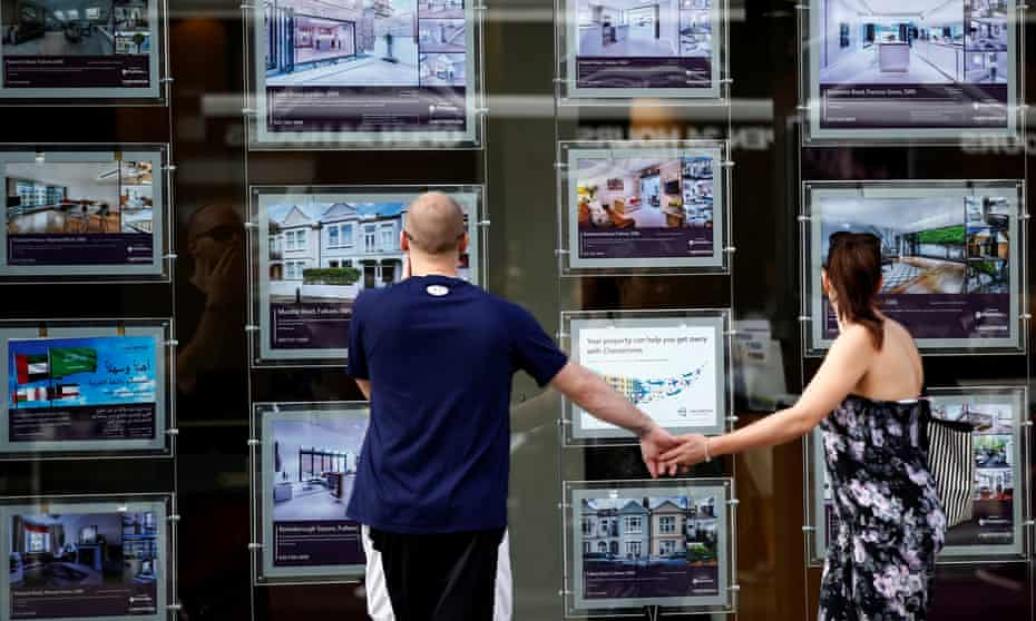 A couple view properties for sale in an estate agents window in London.