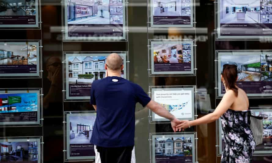 A couple look in an estate agent's window.