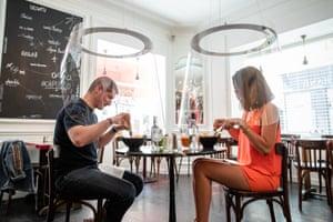 Diners sit under plexiglass bubbles at the H.A.N.D restaurant in Paris, France.