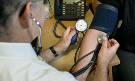GP checking patient's blood pressure