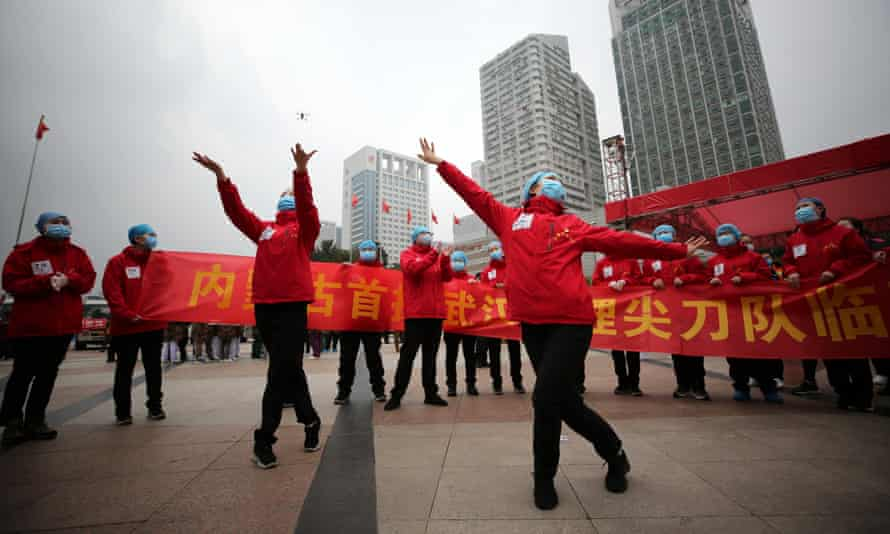 Medical workers celebrate the shutting down of a temporary hospital for coronavirus patients in Wuhan.
