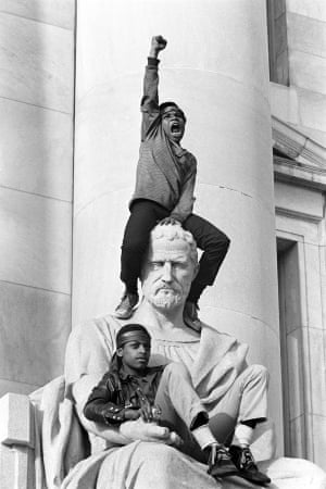 Boy gives raised fist salute on a statue in front of the New Haven County Courthouse during a protest against the Bobby Seale and Ericka Huggins trial, New Haven, Connecticut, May 1, 1970
