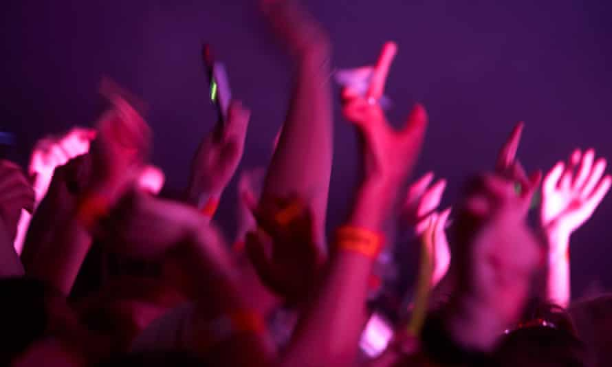 Arms and hands waving in the air at a music event