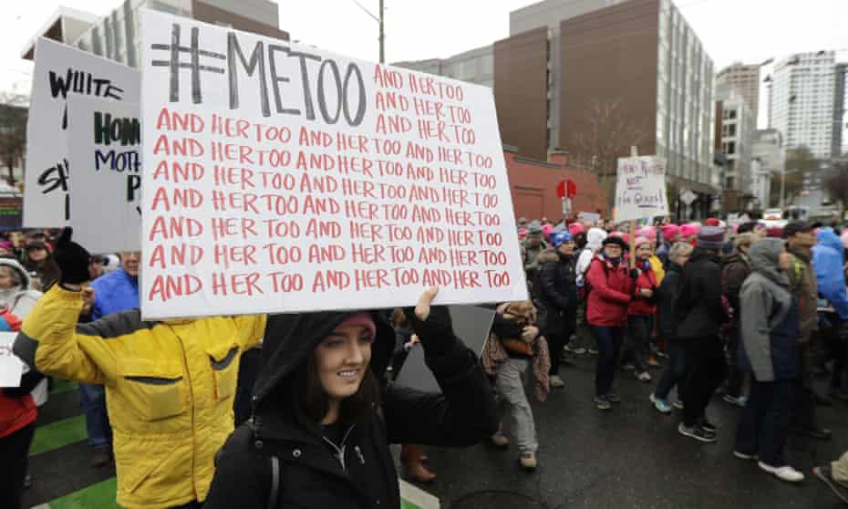 A woman carries a sign with the #MeToo slogan used by people speaking out against sexual harassment