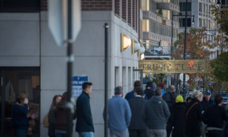 People stand in line outside a polling station located at Trump Place on election day in New York.
