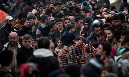 Refugees and migrants queue for food at the Greek-Macedonian border on Friday.