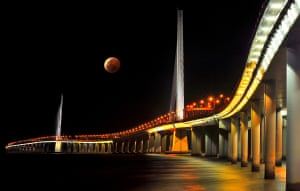 Zhiwen Huang, China Special Mention, Cities: Architecture and Spaces. Rising red moon watching over the bridge across the bay. Nanshan district, Shenzhen city, China.