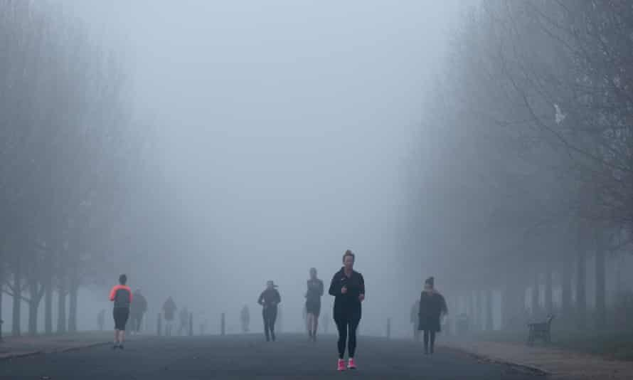 People jog amid dense fog in London.